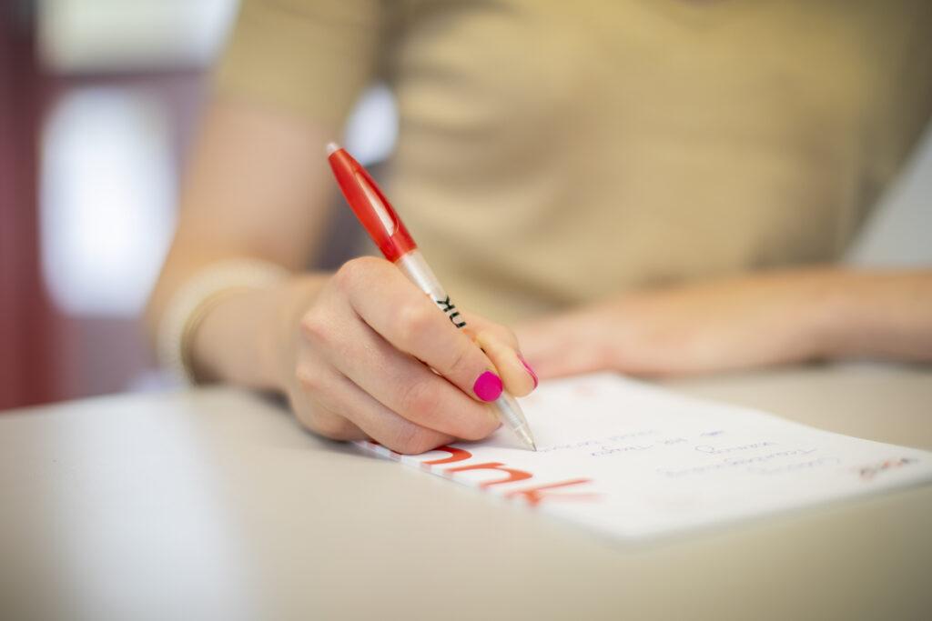 Deelnemen aan een schriftelijke proef - iemand die schrijft op een blok papier